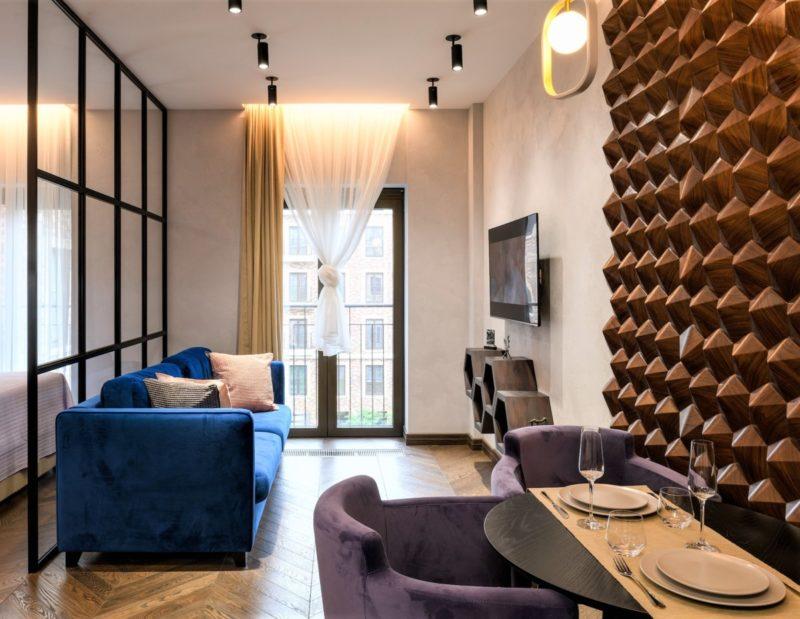 Белая минеральная штукатурка в гостиной квартиры - студии фото интерьера